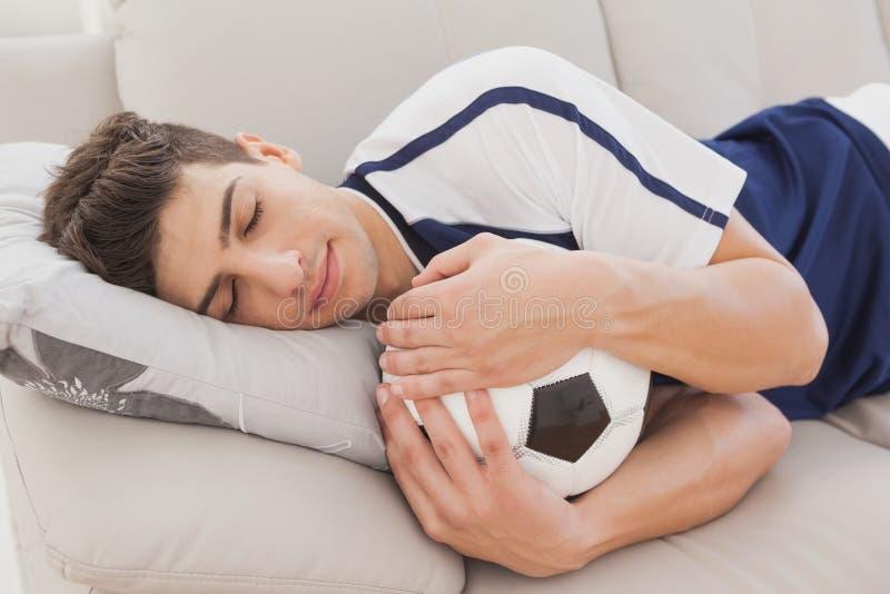 Football fan sleeping with ball stock photos