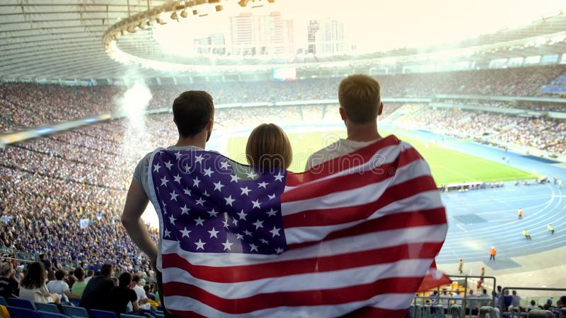 Football fans with American flag jumping at stadium, cheering for national team stock images