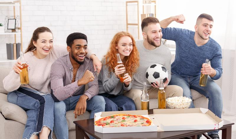 Football fans cheering sport league and drinking beer. Enjoying weekend at home stock photography