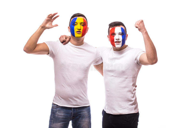 Football fans of France and Romania national teams friendly suport together the game of their teams at match. On white background. European football fans royalty free stock photography