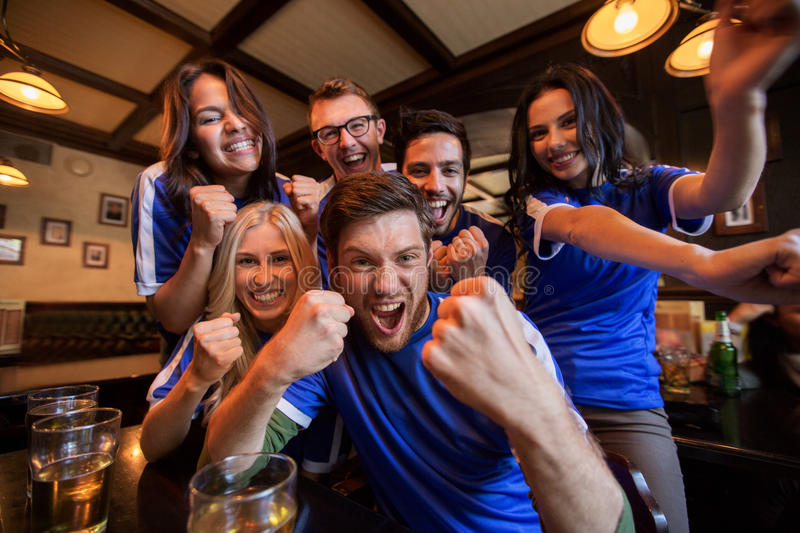 Football fans or friends with beer at sport bar stock photo