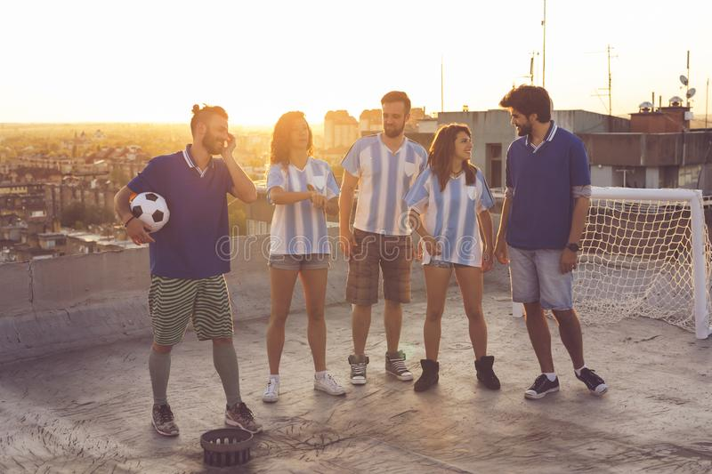 Football fans having fun. Group of young friends having fun on a building rooftop after a football match; jumping, all caught in the air with the cityscape and stock images