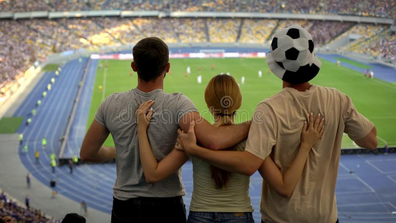 Football fans hugging at stadium, friends cheering victory of favorite team. Stock photo royalty free stock photography