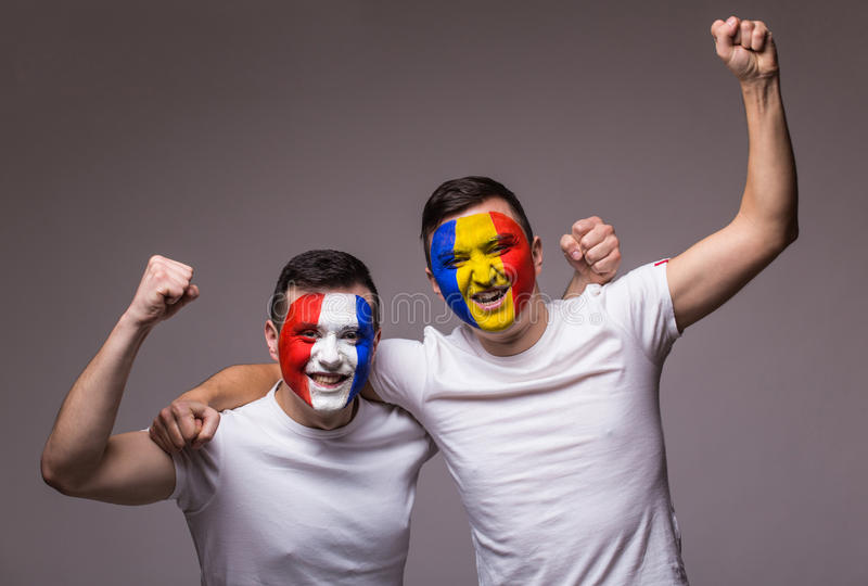 Football fans of Romania and France national teams celebrate, dance and scream. France vs Romania. Football fans of Romania and France national teams celebrate royalty free stock photos