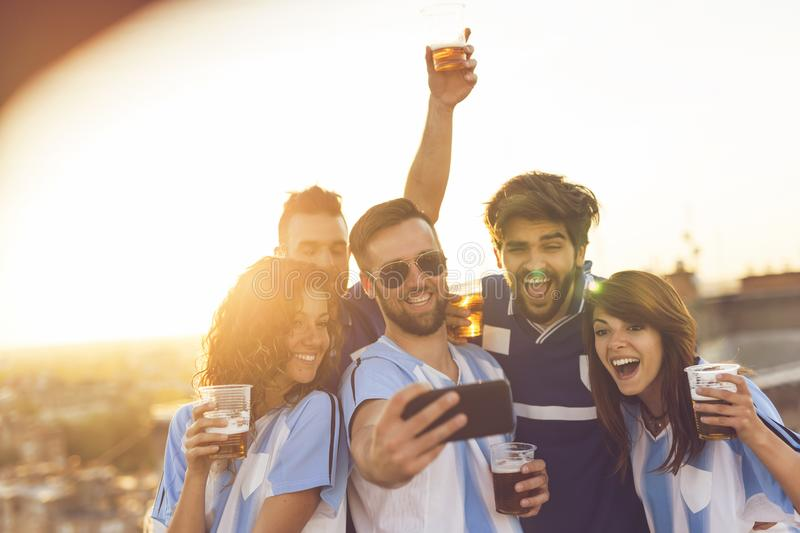 Football fans taking a selfie. Group of football fans drinking beer and having fun before the game, taking a selfie on a building rooftop terrace stock photo