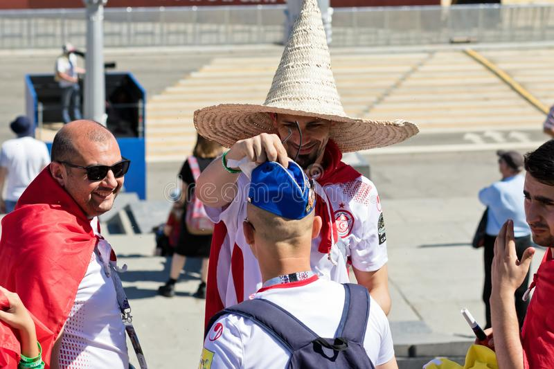 Football fans of Tunisia and England are changing their hats on royalty free stock photography