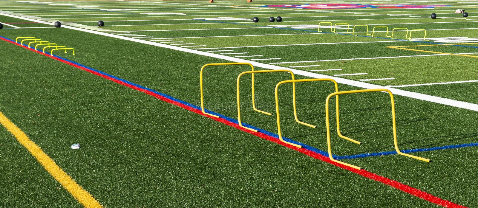 Football field set up with mini hurdles and medicine balls. A green turf football field is set up with medicine balls and yellow mini hurdles for strength, speed stock photos