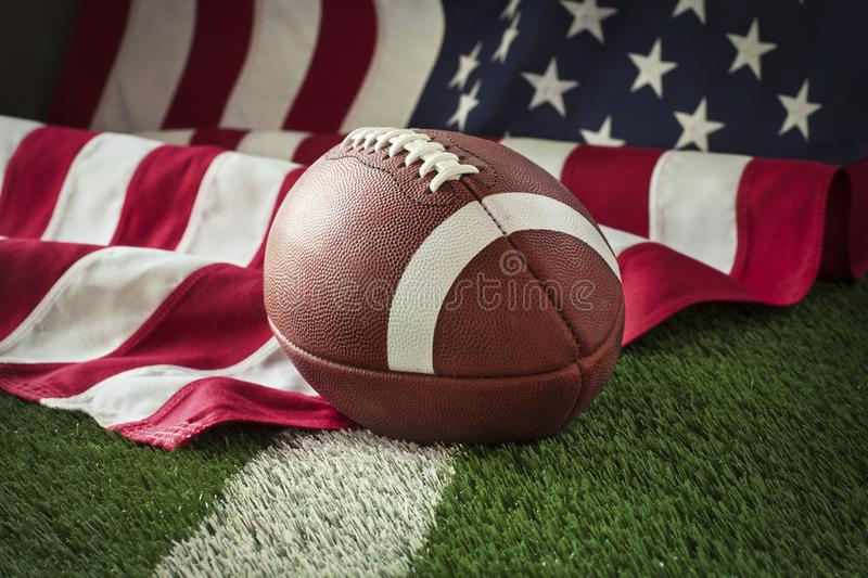 Football on field with stripe and American flag behind stock photos