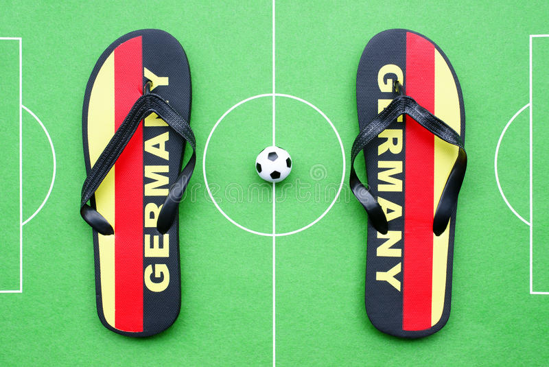 Football flip flops. A football or soccer field with a ball and flip flops with the German flag and the text Germany stock images