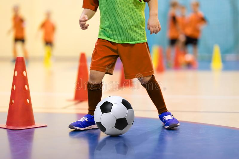 Football futsal training for children. Boys training dribble skills. Football futsal training for children. Soccer training dribbling cone drill. Indoor soccer stock photography