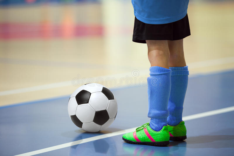 Football futsal training for children. Indoor soccer young player. With a soccer ball in a sports hall. Player in blue uniform. Sport background stock image
