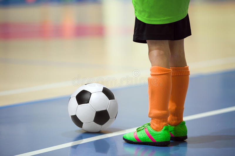 Football futsal training for children. Indoor soccer young player. With a soccer ball in a sports hall. Sport background stock image