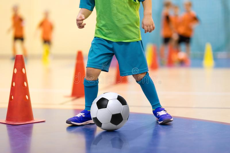Football futsal training for children. Soccer training dribbling cone drill. Indoor soccer young player with a soccer ball in a sports hall. Player in blue royalty free stock photo