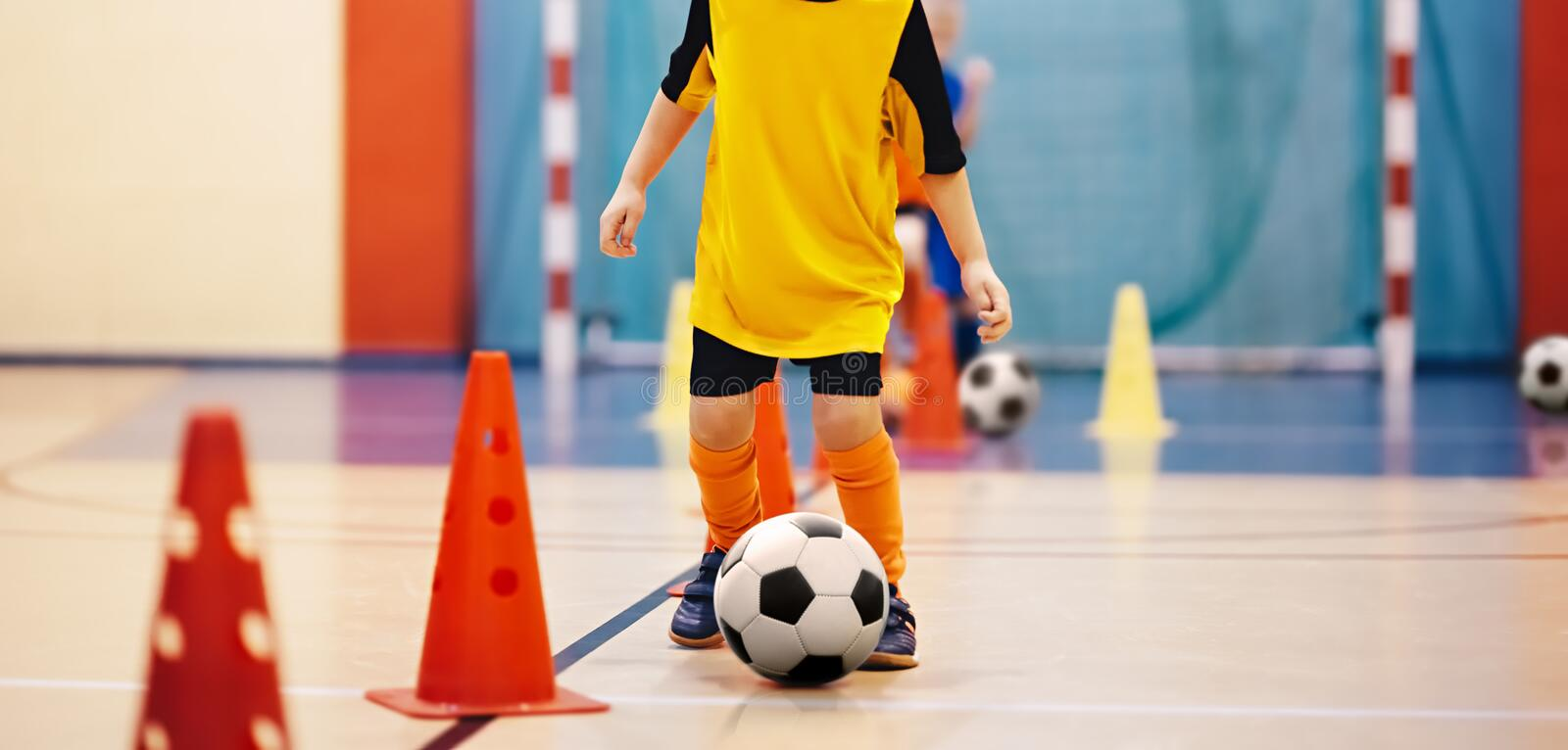 Football futsal training for children. Soccer training dribbling cone drill. Indoor soccer young player with a soccer ball in a sports hall. Player in orange royalty free stock photos