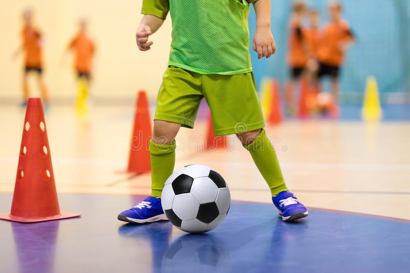 Football futsal training for children. Soccer training dribbling. Cone drill. Indoor soccer young player with a soccer ball in a sports hall. Player in yellow stock photos