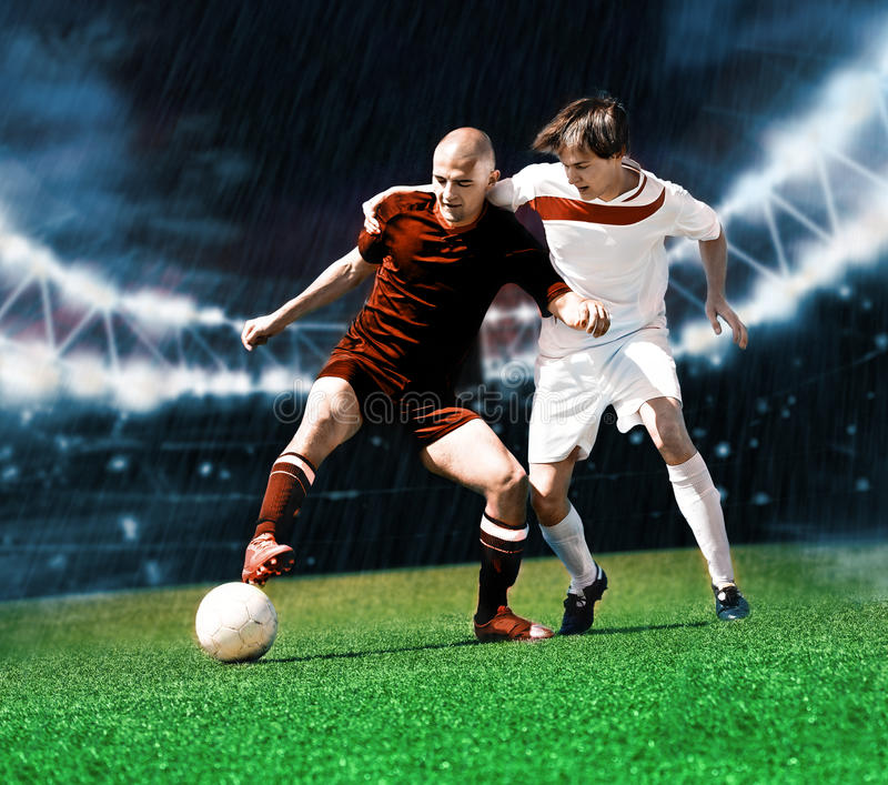 Football game. Two football players from opposing team on the field stock photography