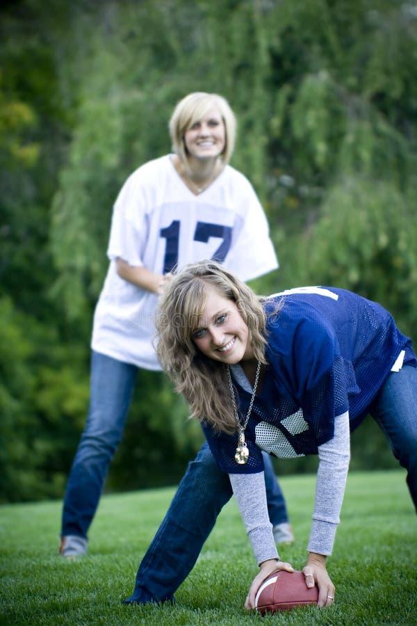 Football Girls. Two attractive women play a little backyard football stock photo