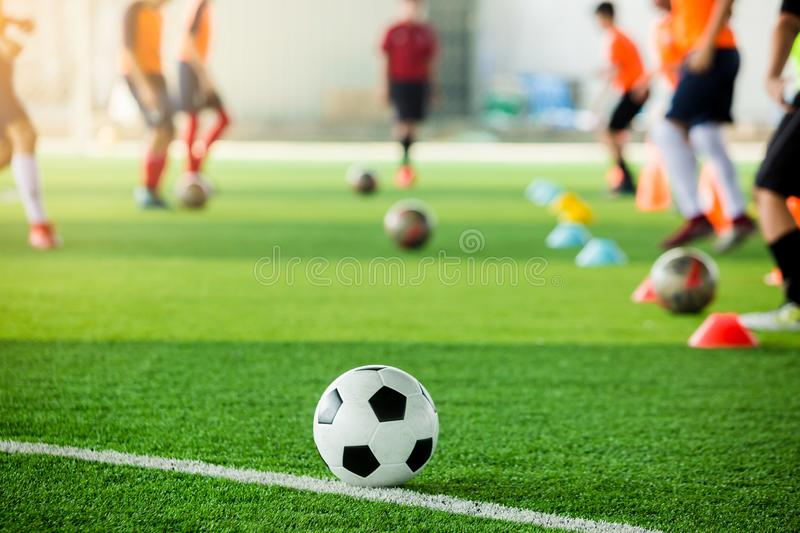 Football on green artificial turf with blurry soccer team training. Blurry kid soccer player jogging between marker cones and control ball with soccer royalty free stock photography