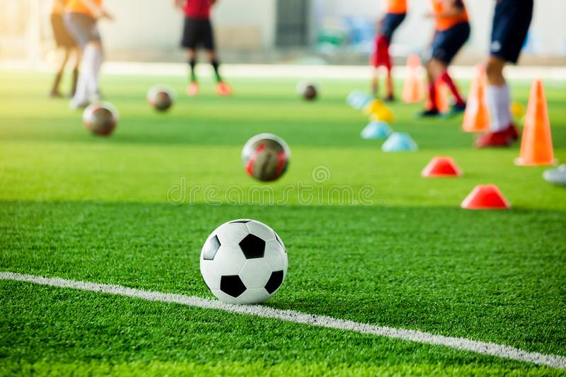 Football on green artificial turf with blurry soccer team training. Blurry kid soccer player jogging between marker cones and control ball with soccer stock photo