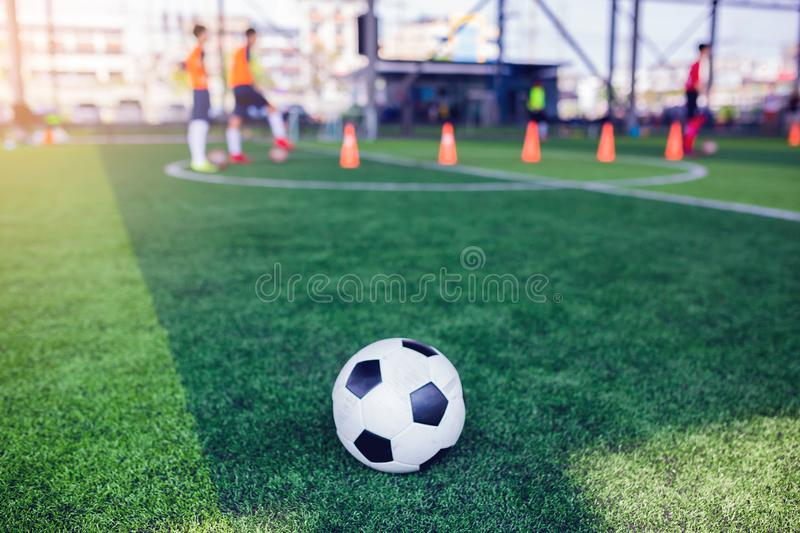 Football on green artificial turf with blurry soccer team training, blurry kid soccer player jogging between marker cones stock photo