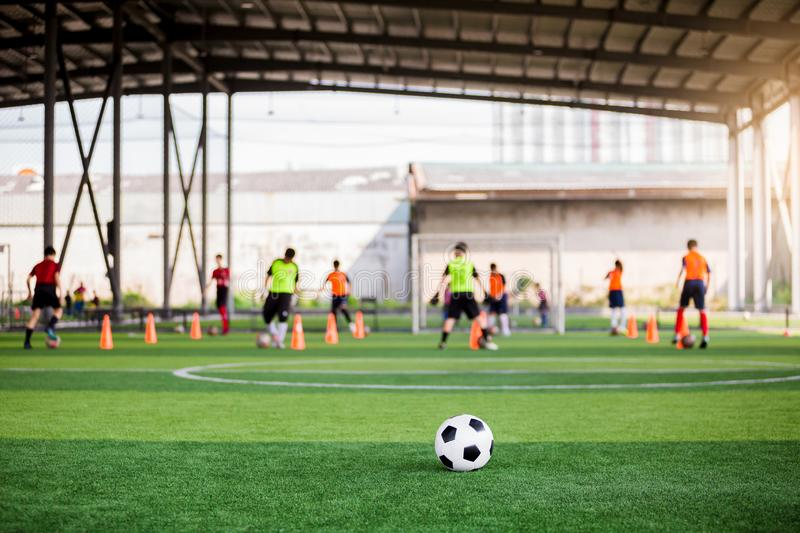 Football on green artificial turf with blurry soccer team training. Blurry kid soccer player jogging between marker cones and control ball with soccer royalty free stock photo