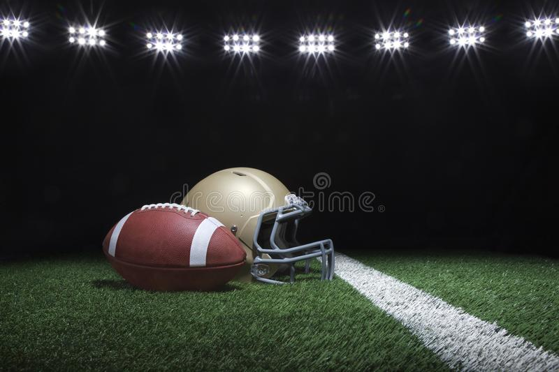 Football and helmet on grass field below stadium lights at night royalty free stock photo