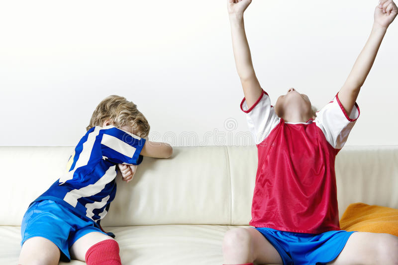 Football kids supporting different teams. Two kids supporting different teams watching football and celebrating at home royalty free stock images