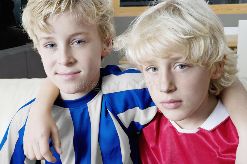 Football kids supporting different teams. Portrait of two kids wearing soccer uniforms of different teams stock photo
