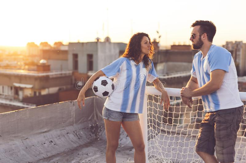 Football and love. Couple in love wearing football jerseys, standing on a building rooftop after a match and enjoying a beautiful sunset over the city royalty free stock photography