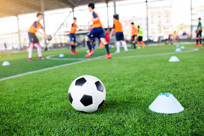 Football between marker cones on green artificial turf with blurry soccer team training. Blurry kid soccer player jogging between marker cones and control ball royalty free stock photo