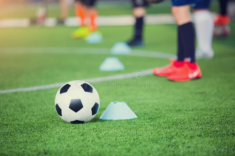 Football between marker cones on green artificial turf with blurry soccer team training. Blurry kid soccer player jogging between marker cones and control ball stock photography