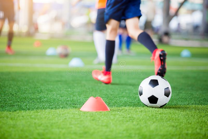 Football between marker cones on green artificial turf with blurry soccer team training. Blurry kid soccer player jogging between marker cones and control ball royalty free stock photos