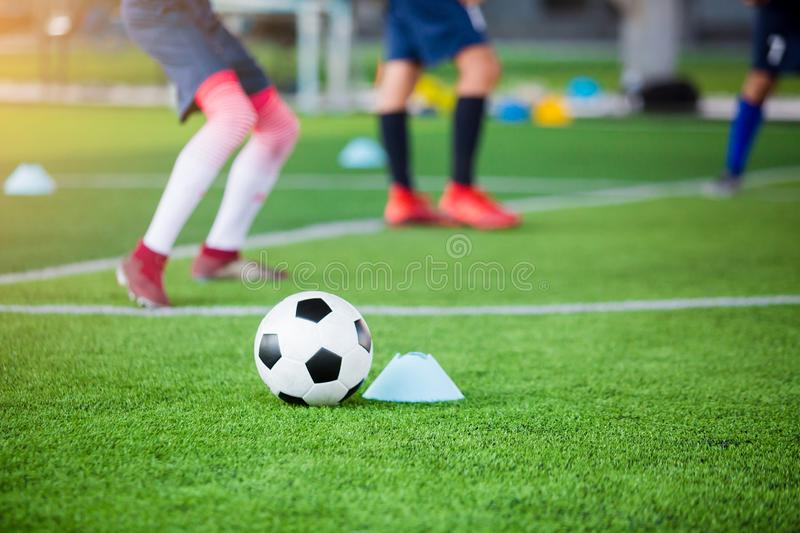 Football between marker cones on green artificial turf with blurry soccer team training. Blurry kid soccer player jogging between marker cones and control ball royalty free stock images