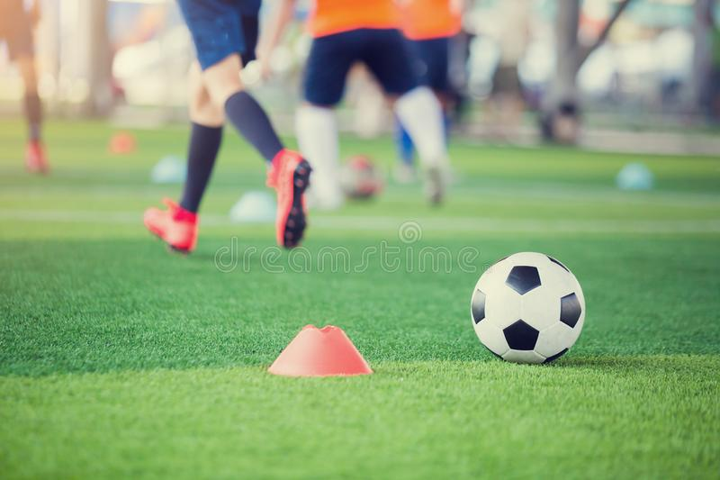 Football between marker cones on green artificial turf with blurry soccer team training. Blurry kid soccer player jogging between marker cones and control ball royalty free stock image
