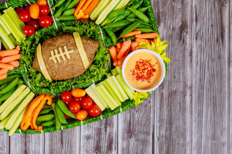 Football meatloaf with vegetable and dipping for Super Bowl fan party. Football meatloaf with fresh vegetable platter and dipping for Super Bowl fan party stock images