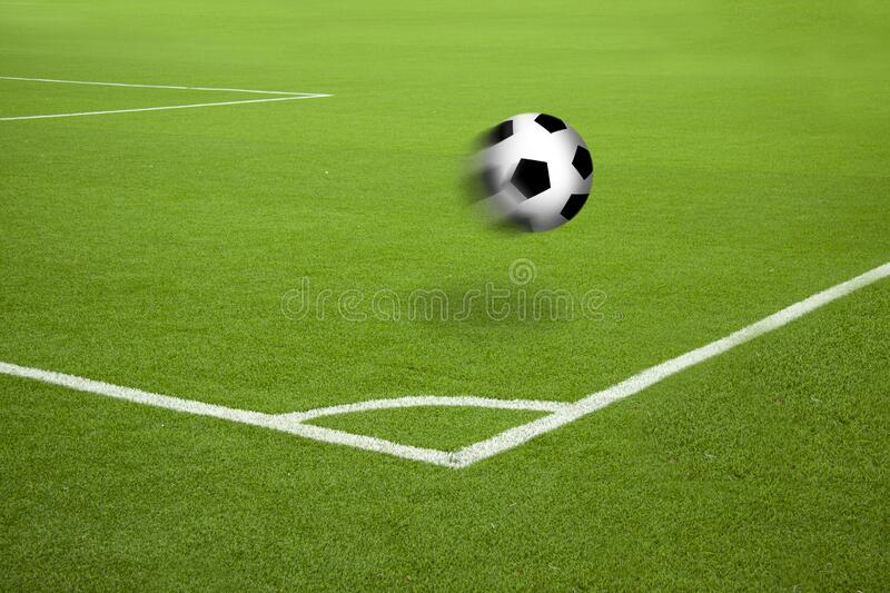 Football in motion on soccer court with white stripes corner markings. stock images