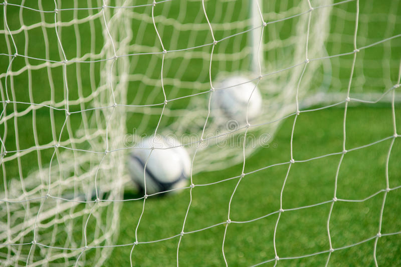 Football net with out-focus balls in background. In a training session stock photo