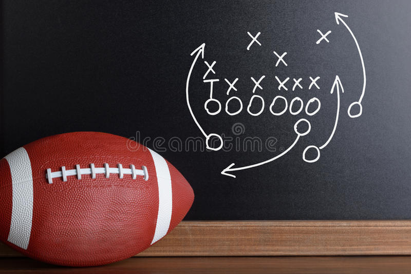 Football play strategy drawn out on a chalk board. With Rugby Ball royalty free stock photography
