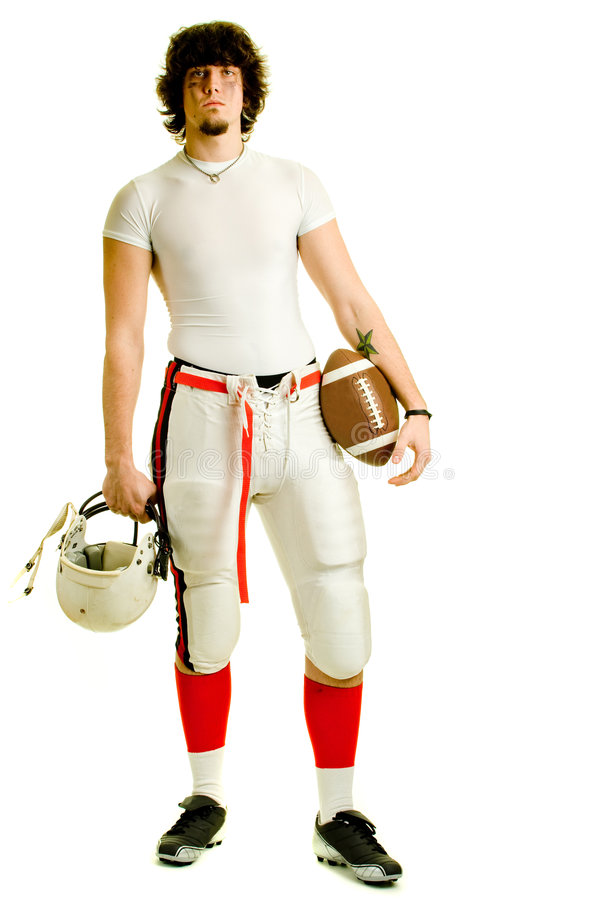 Football Player. An American football player. Standing with helmet and ball royalty free stock photography