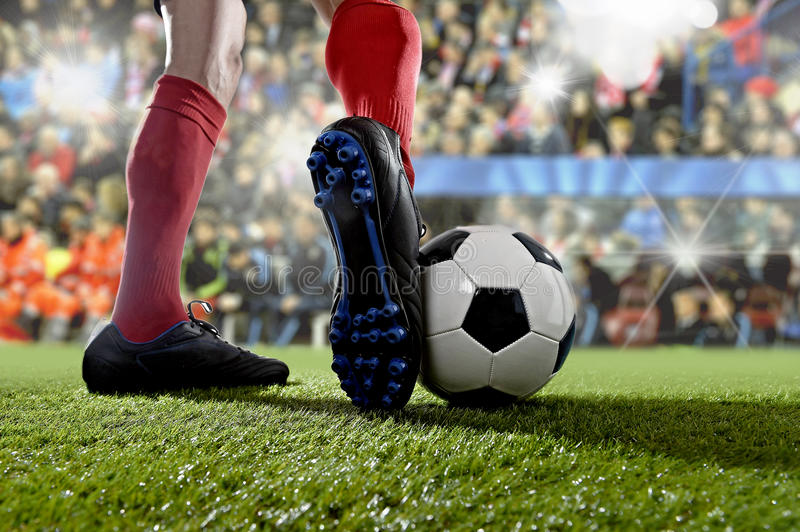 Football player in action running and dribbling at soccer stadium playing match. Close up legs and feet of football player in action wearing blue socks and black stock photo