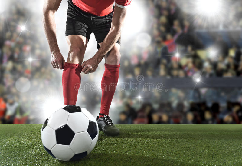 Football player with ball wearing black shoes adjusting his red sock standing on stadium pitch stock photo