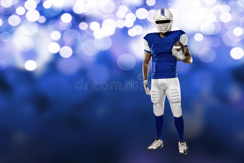 Football Player. With a blue uniform on a blue lights background stock photography