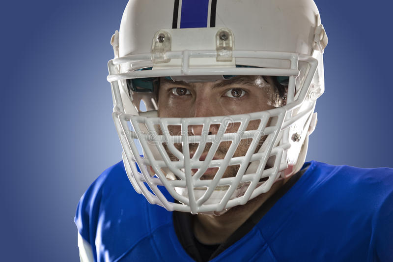 Football Player. Close up in the eyes of a Football Player with a blue uniform on a blue background stock images