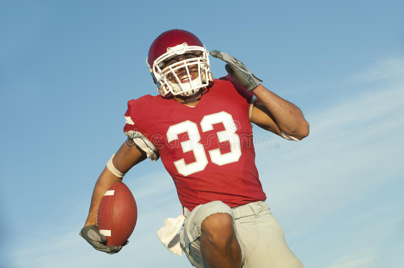 Football player in game action. Football player running with the ball stock photo