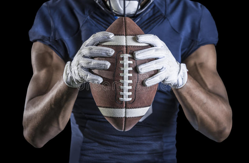 Football Player holding a football tightly at his chest stock photo