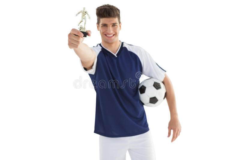 Football player holding winners trophy royalty free stock photo