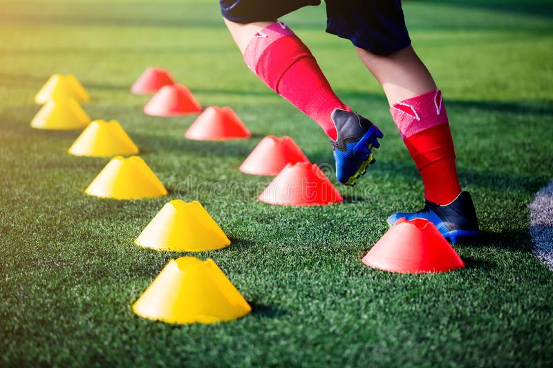 Football player Jogging and jump between cone markers on green a royalty free stock photos