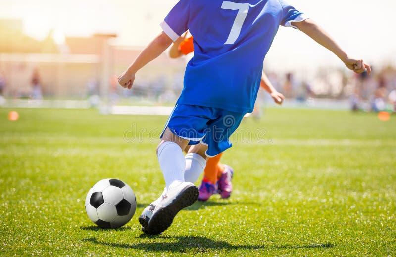 Football Player Kicking Ball on Grass Pitch. Soccer Striker Scoring Goal stock images