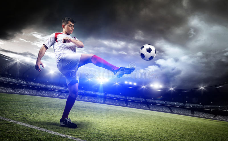 Football player is kicking a ball in the stadium. The imaginary stadium is modelled and rendered royalty free stock image