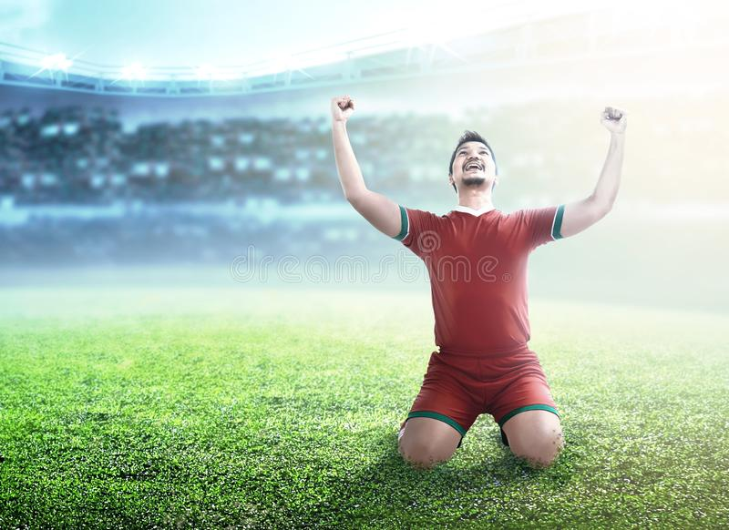 Football player man celebrate his goal with raised arms and kneeling. On the football field at stadium royalty free stock photos